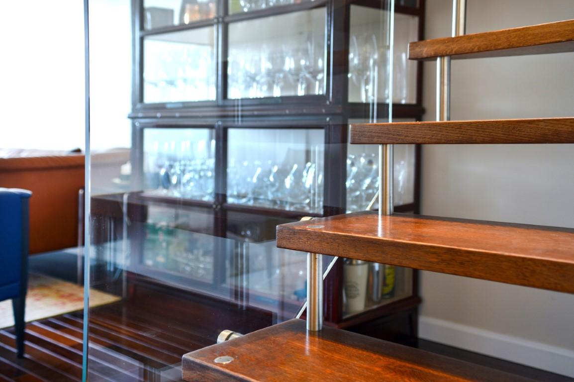 מדרכי עץ אלון בגוונים של חום כתום, ספייסרים מנירוסטה ומעקה זכוכית שקופה