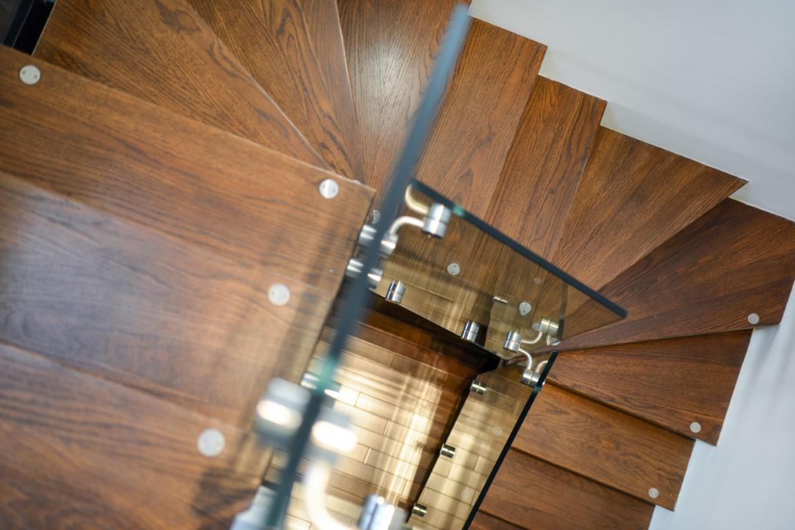 מבט על דרך מדרגות העץ ומעקה הזכוכית מהקומה העליונה אל רצפת הפרקט בתחתית