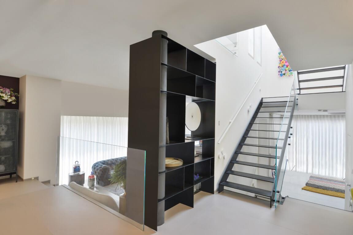 שני גרמי מדרגות ברזל שחורות עם מעקות מזכוכיתמחברים בין מפלסי הוילה