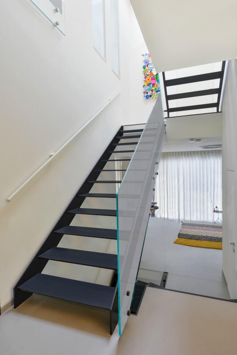שני גרמי מדרגות ברזל שחור עולים מהסלון אל הקומה העליונה בליווי של מעקה זכוכית שקופה