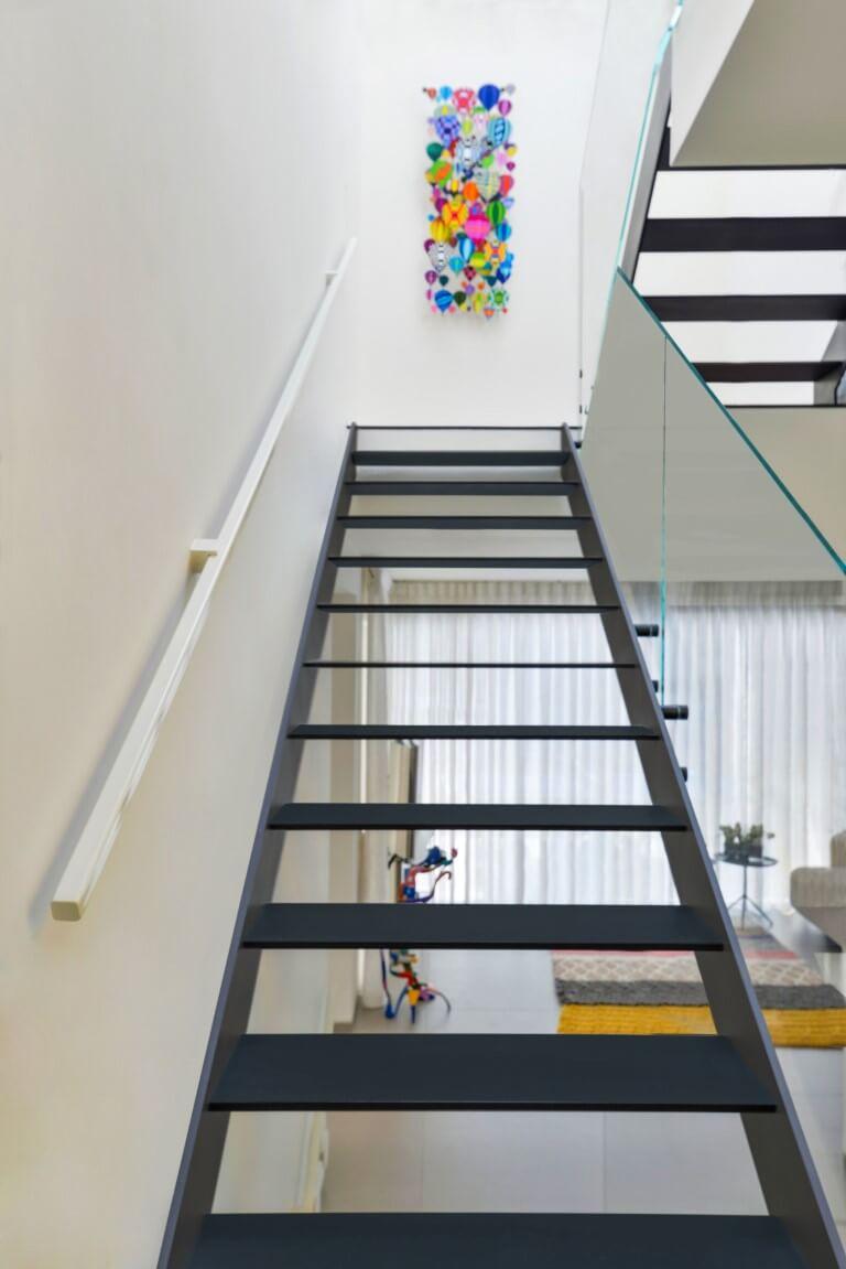 תמונה צבעונית על קיר לבן במעלה גרם מדרגות הברזל השחור על רקע סלון הוילה