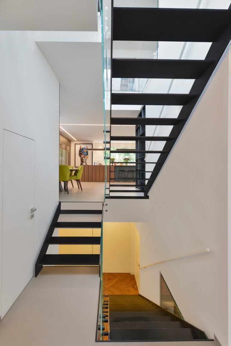 שלושת גרמי מדרגות הברזל יוצרים מפגש בין הקומה התחתונה והסלון המינימליסטי