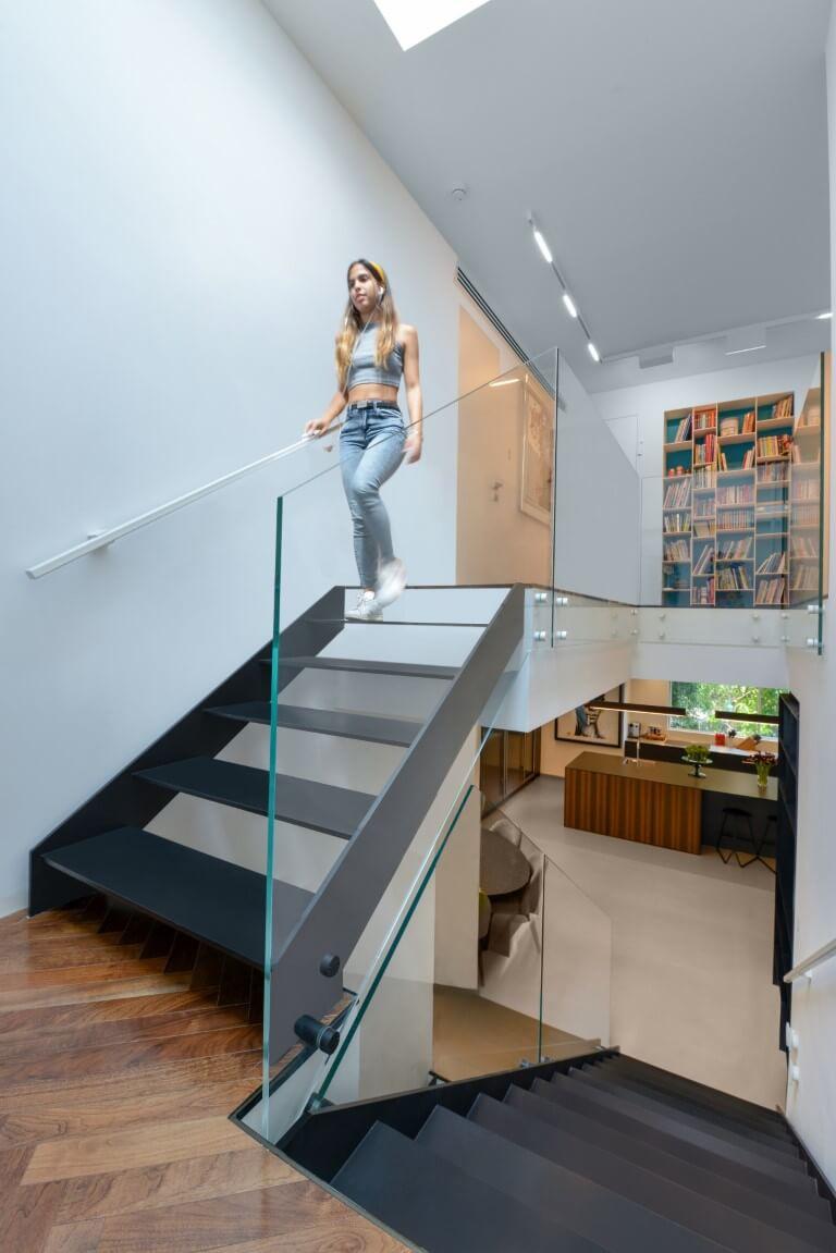 יורדת במדרגות הברזל מהקומה העליונה בעודה נאחזת במאחז היד הבלן שבולט מהקיר