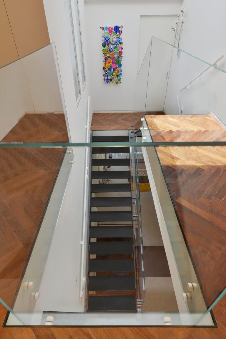 מבטח מהקומה העליונה דרך מעקה הזכוכית על גרם מדרגות הברזל השחורות