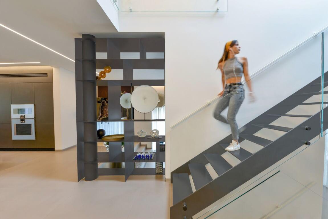 יורדת במדרגות הברזל ושולחת מבט לקומה העליונה