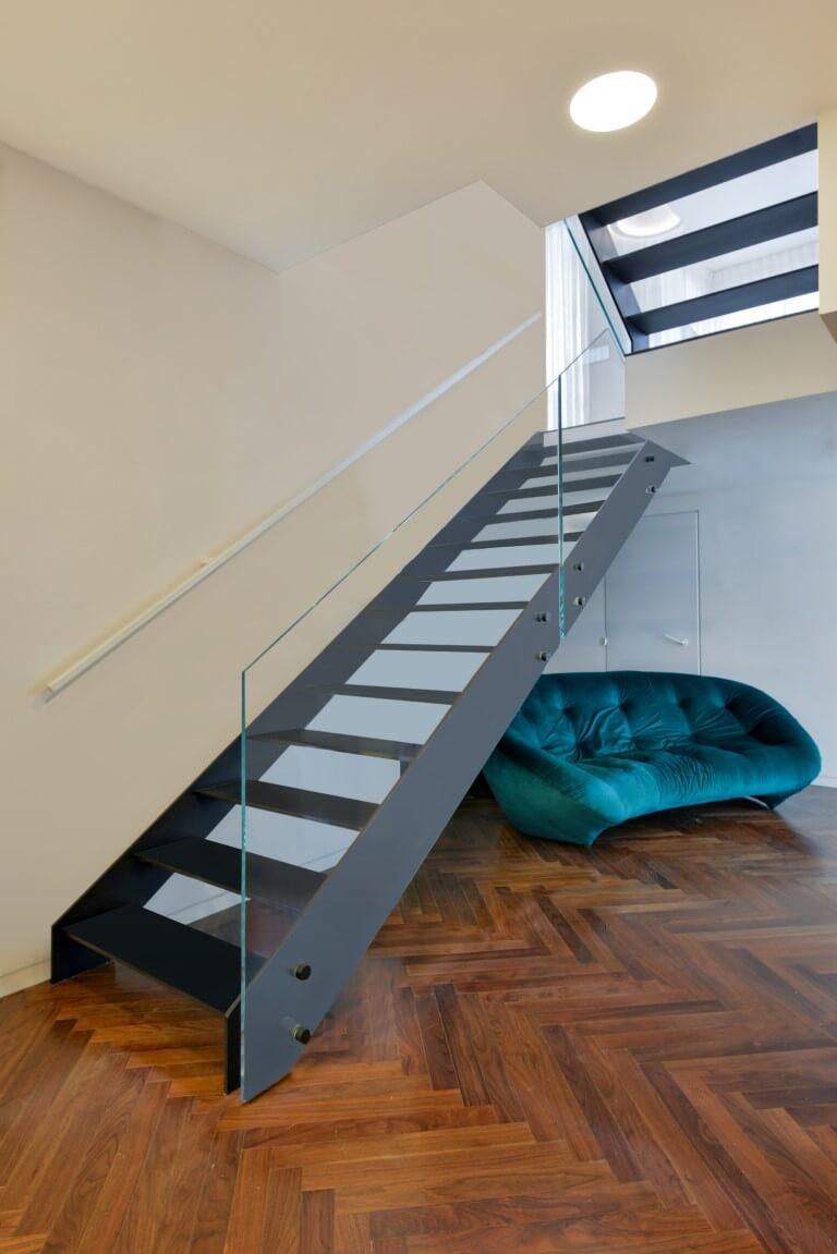 הספה בירוק פרסי מסתתרת ביו הפרקט הג'ינג'י ומדרגות הברזל השחור