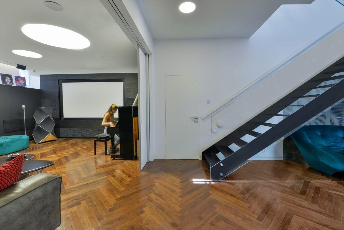 מבט רחב על הסלון, הפסנתר ומדרגות הברזל השחורות