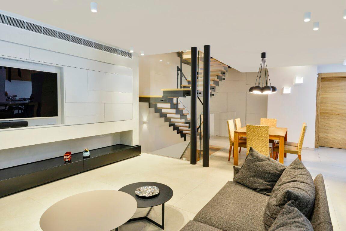 מבט מהסלון אל עבר פינת האוכל והפיר שמכיל בתוכו מדרגות ברזל שחורות עם מדרכי עץ אלון טבעי בהיר ומעקה זכוכית שקופה