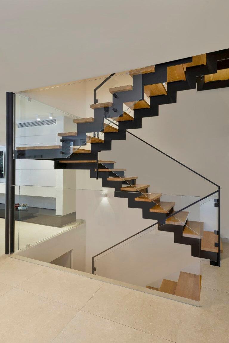 שני גרמי מדרגות קונסטרוקצית ברזל עם מדרגות עץ אלון בהיר בליווי של מעקה זכוכית וברזל שחור