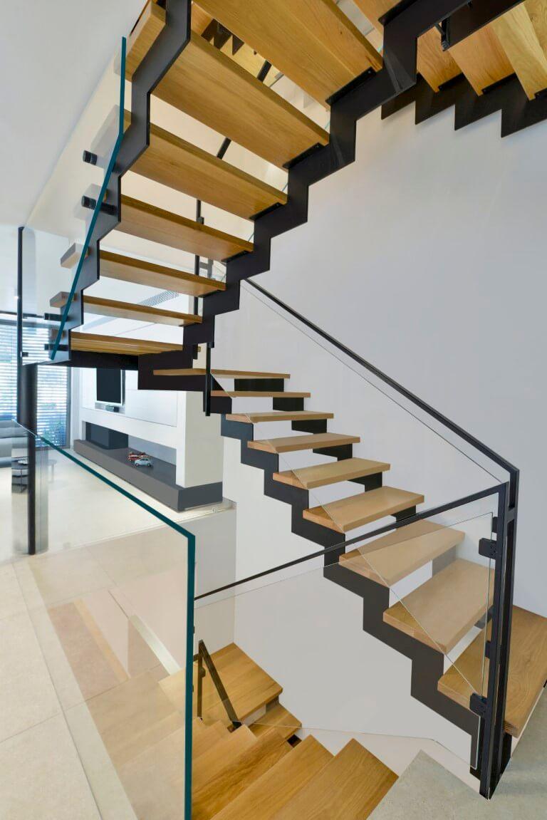חמישה גרמי מדרגות מעץ אלון וברזל שחור מוקפים מעקה בטיחות מזכוכית