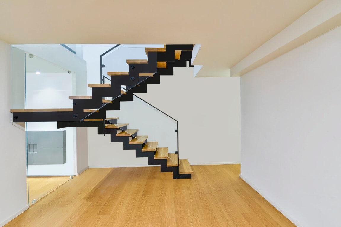 שני גרמי מדרגות ברזל שחור ועץ עם מעקה זכוכית שקופה על גבי פרקט בצבע בהיר טבעי שתואם את צבעי מדרכי המדרגות