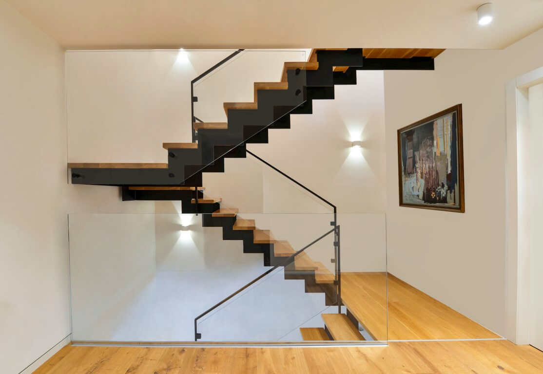 מבט רחב על פיר מדרגות הברזל והעץ שפוגש במפלס תמונה שתלויה על הקיר