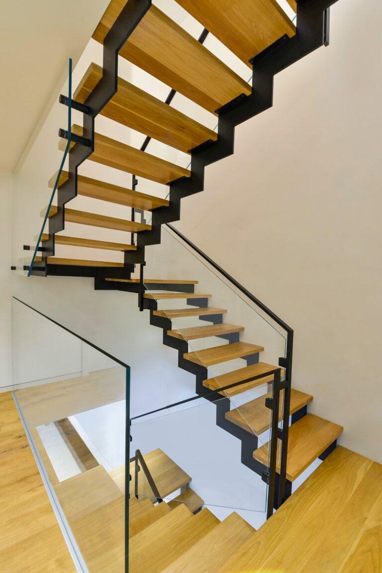 מבט על ארבעה גרמי מדרגות עץ אלון טבעי שמחברים את מפלסי המבנה