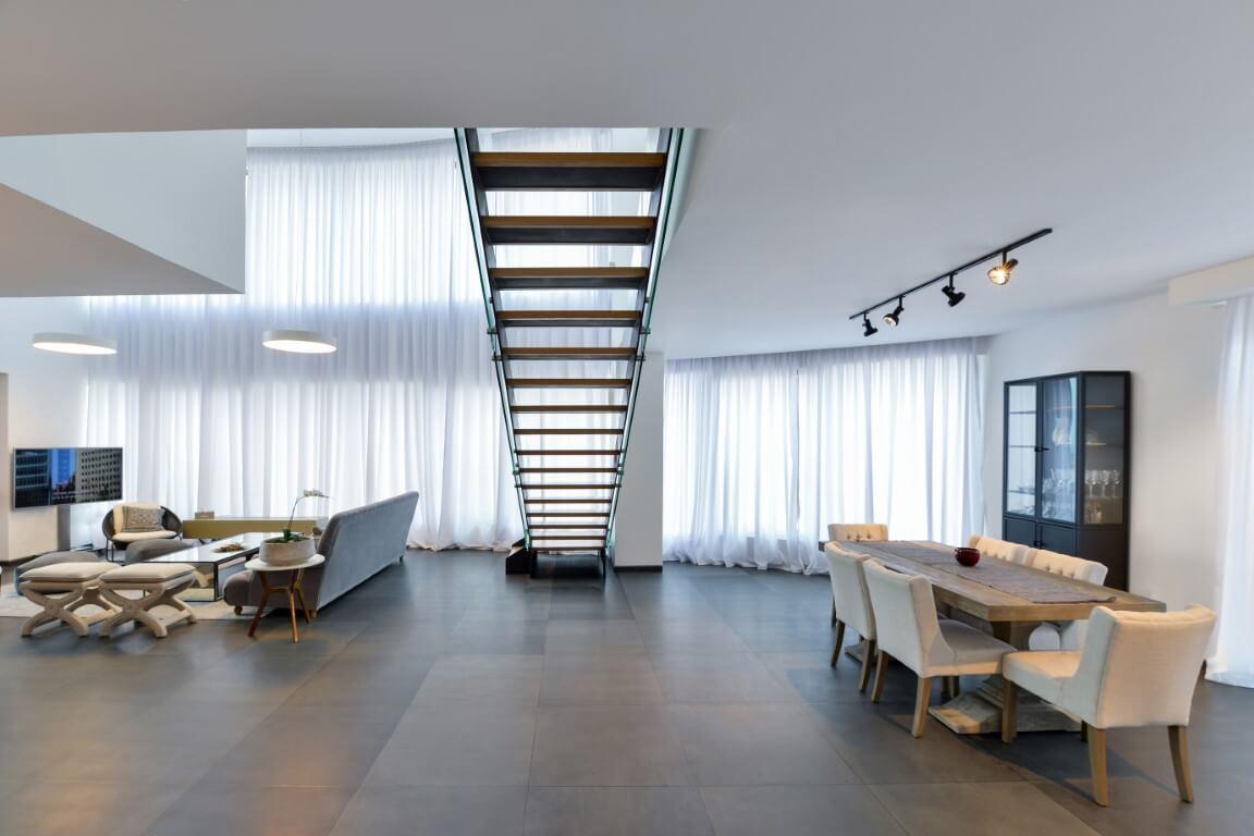 מבט רחב על פינת האוכל והסלון שמתפלצים במרכז באמעצות קונסטרוקצית הברזל של המדרגות