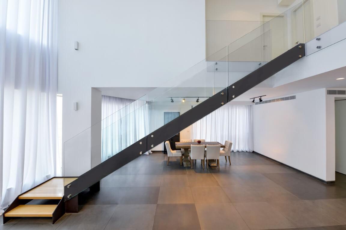 נוף על פינת האוכל מבטד לגרם מדרגות הברזל הארוך שעולה אל המפלס השני בליווי של מעקה זכוכית
