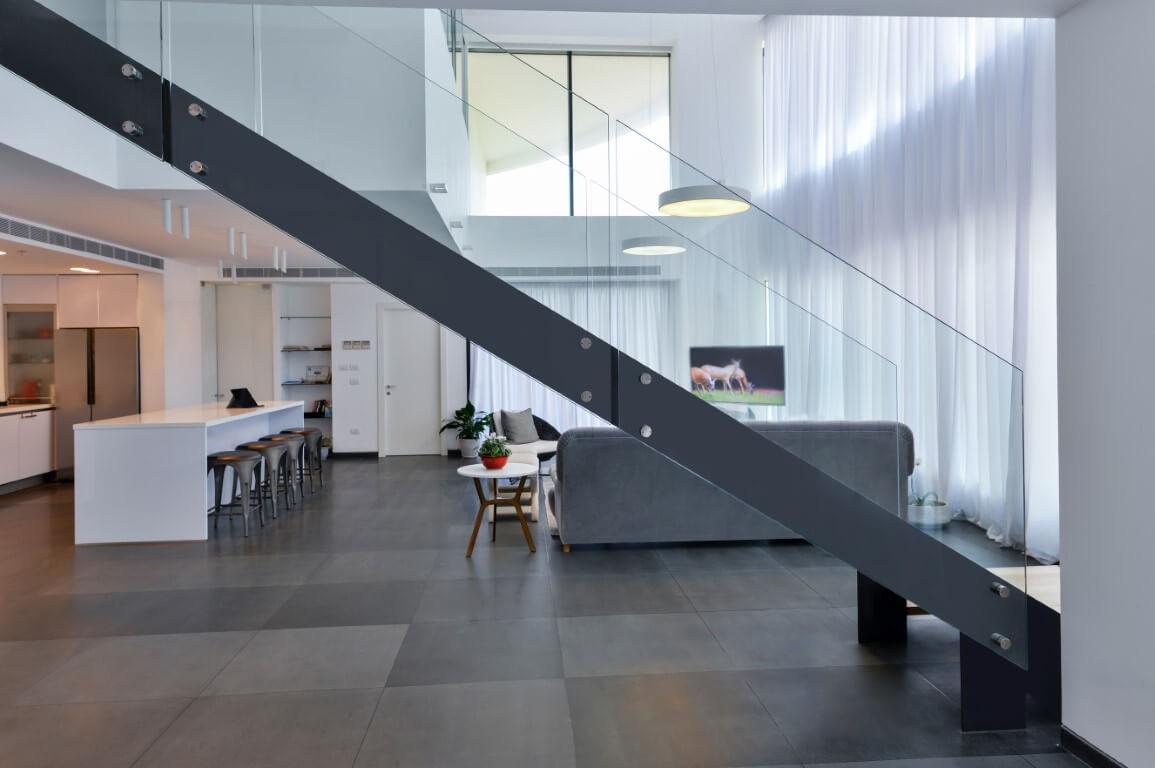 ספת הסלון מסתתרת מאחורי קונסטרוקצית הברזל עליה יושבים מדרכי העץ שבונים את המדרגות בדופלקס