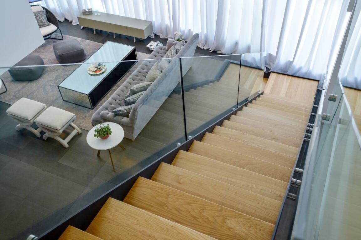 מבט גולש מחלקו העליון של גרם המדרגות דרך השתקפות מדרכי העץ במעקה הזכוכית אל הסלון המפואר במפלס הקרקע