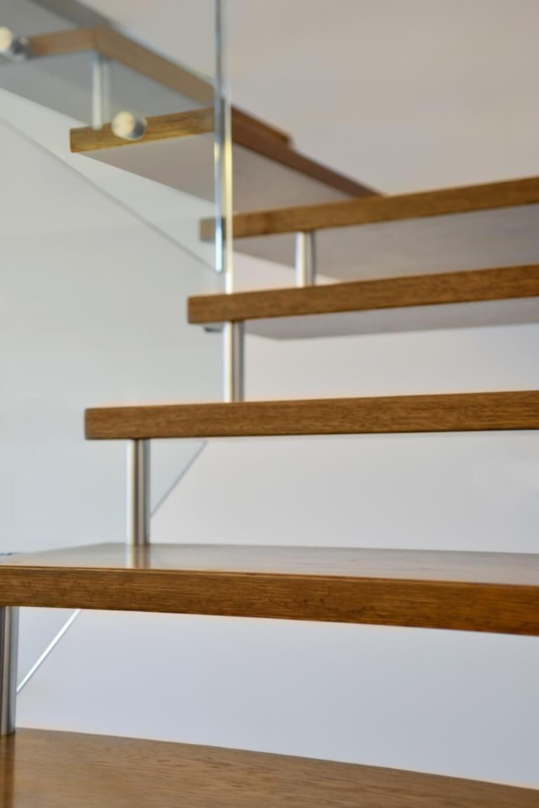 פוקוס על מדרכי מדרגות העץ שמחוברים בספייסרים של נירוסטה