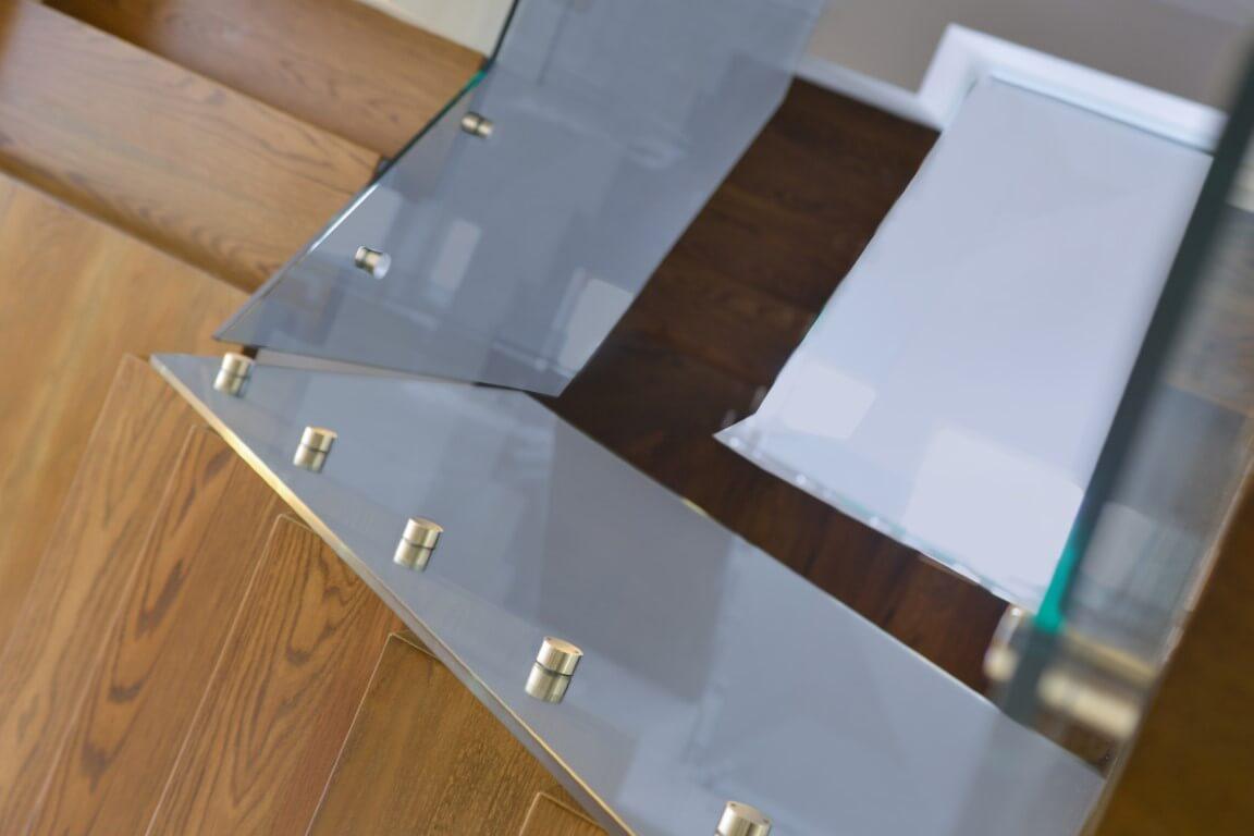 מבט מלמעה על מעקה הזכוכית ופיסה של גרם מדרגות עץ