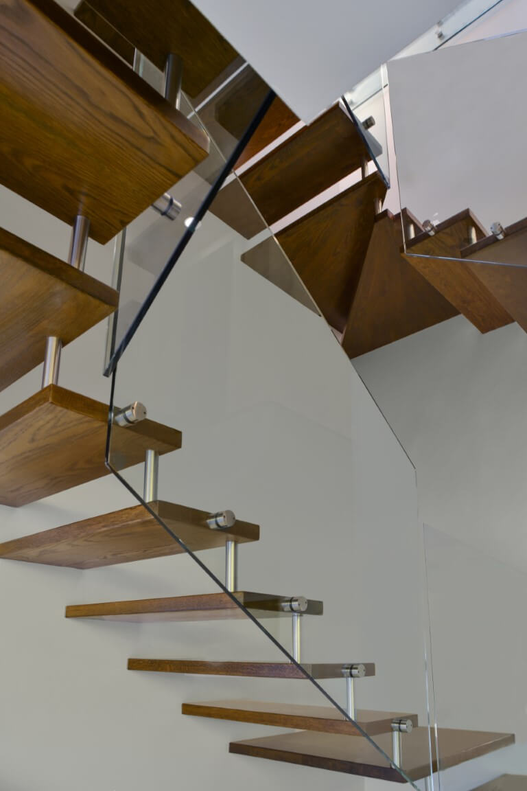 מדרכי מדרגות העץ התלויות שמחוברת למעקה הזכוכית במבט מלמטה