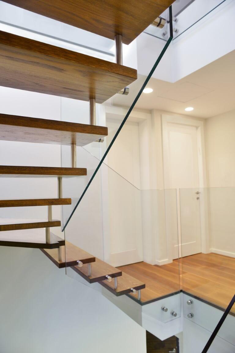 פוקוס צד על מעקה הזכוכית ושני גרמי מדרגות העץ