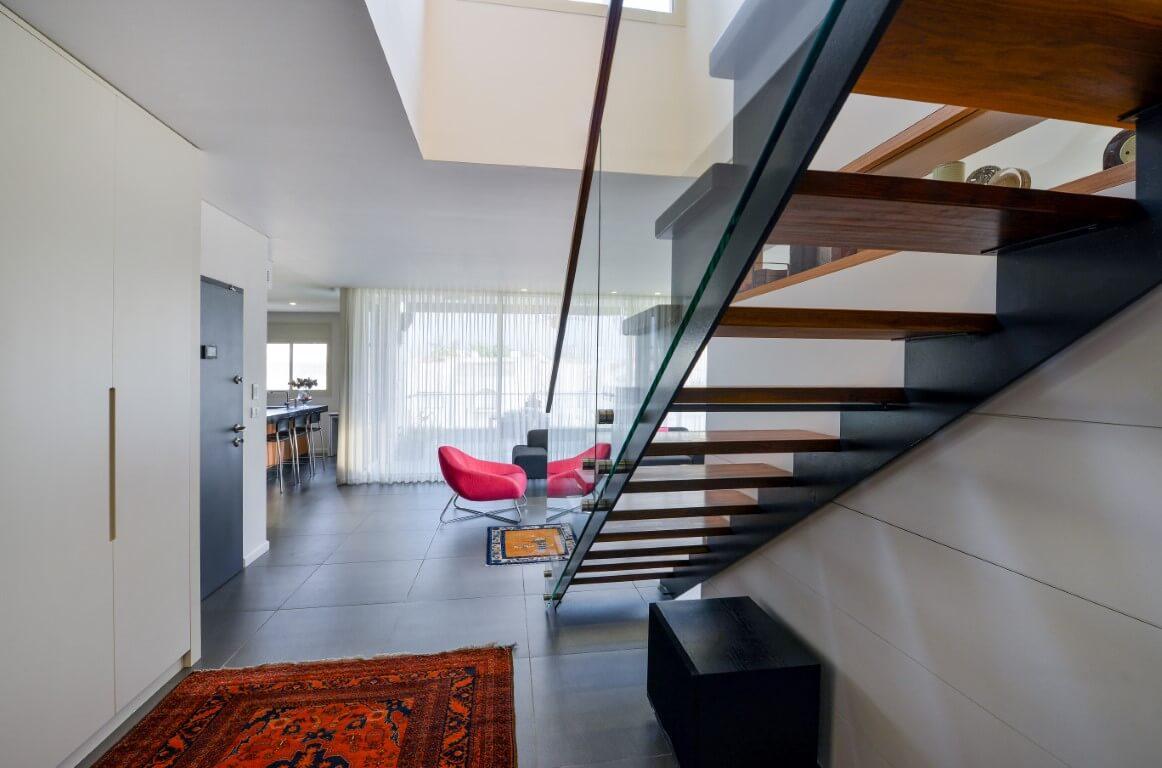 מבט אחורי על מדרכי העץ של המדרגות שיושבות במרכזה של קונסטרוקצית ברזל שחורה ונוף אל הסלון בגוונים של אפור ערפל