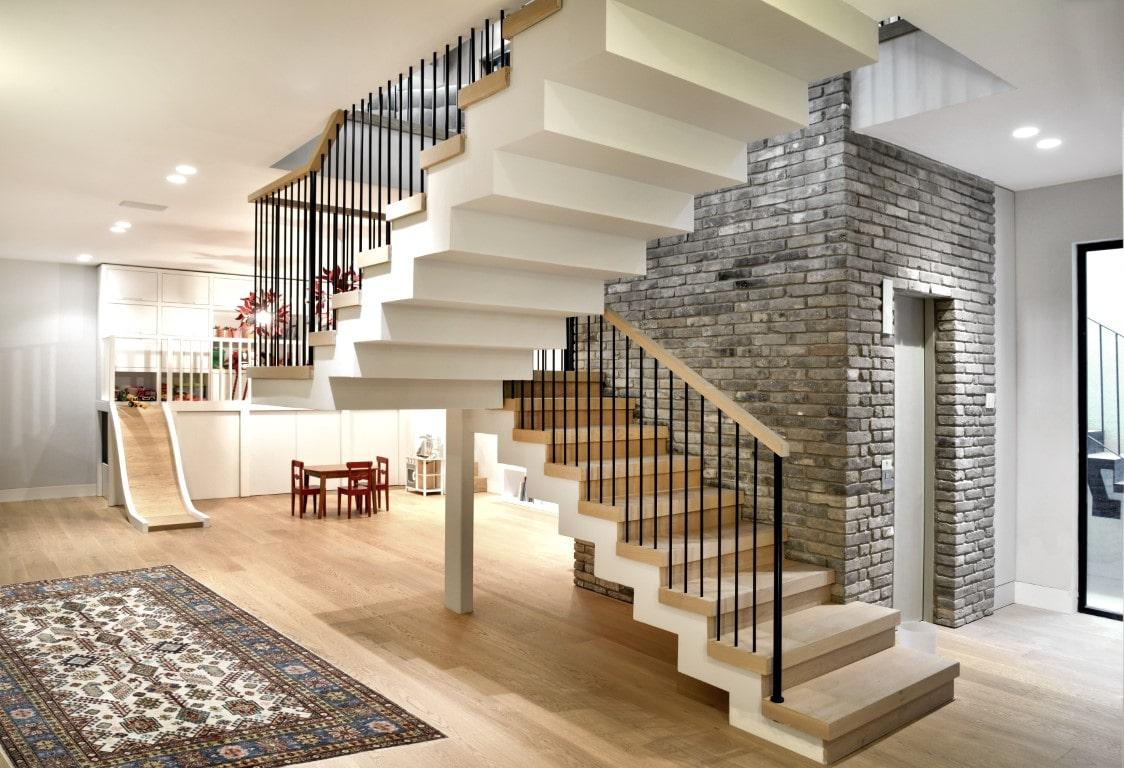 שני גרמי מדרגות ברזל עם מעקה ברזל, מאחז יד מעץ ומדרכי עץ אלון אמריקאי עולים מקומת המרתף אל הקומה השניה בוילה