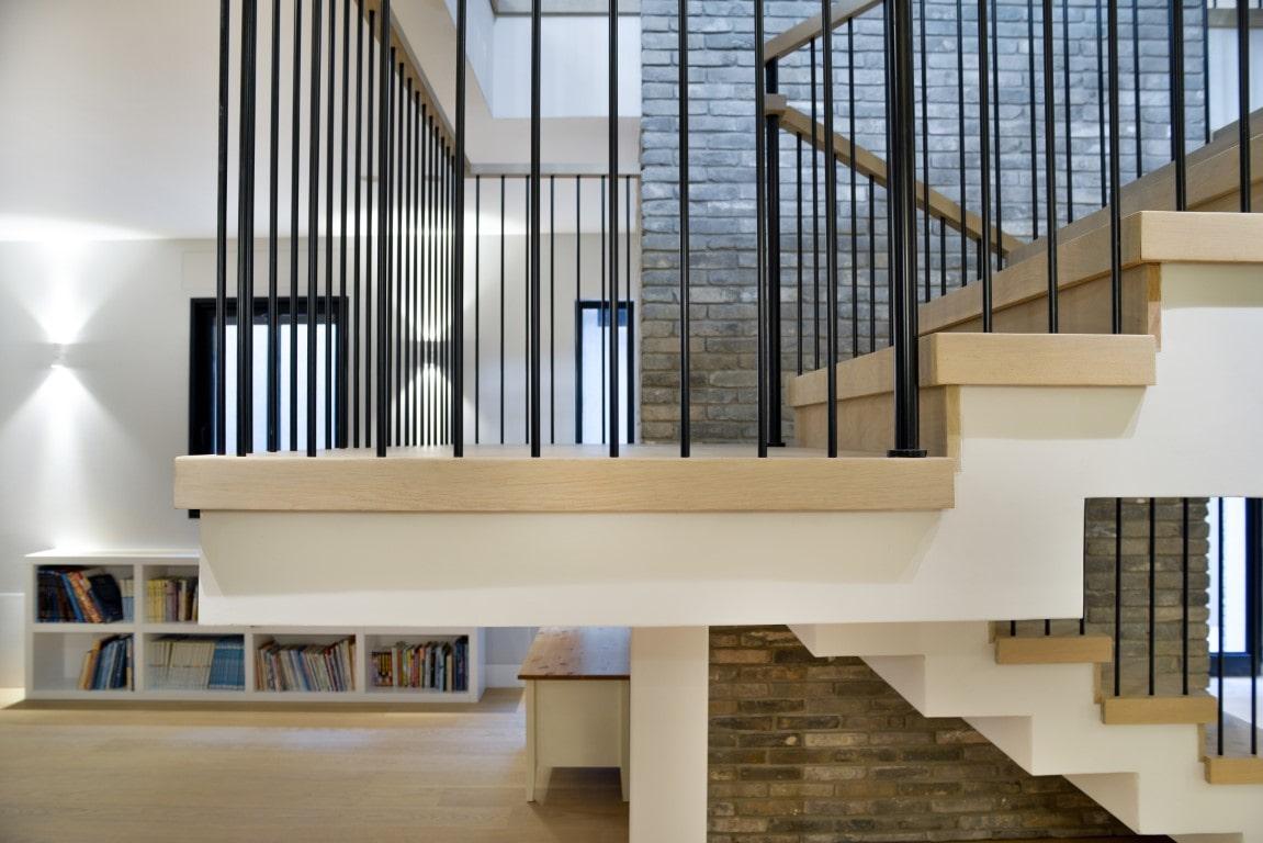 תקריב גרם ביניים שמחבר בין שני גמרי מדרגות ברזל ועץ עם מעקה ברזל שחור