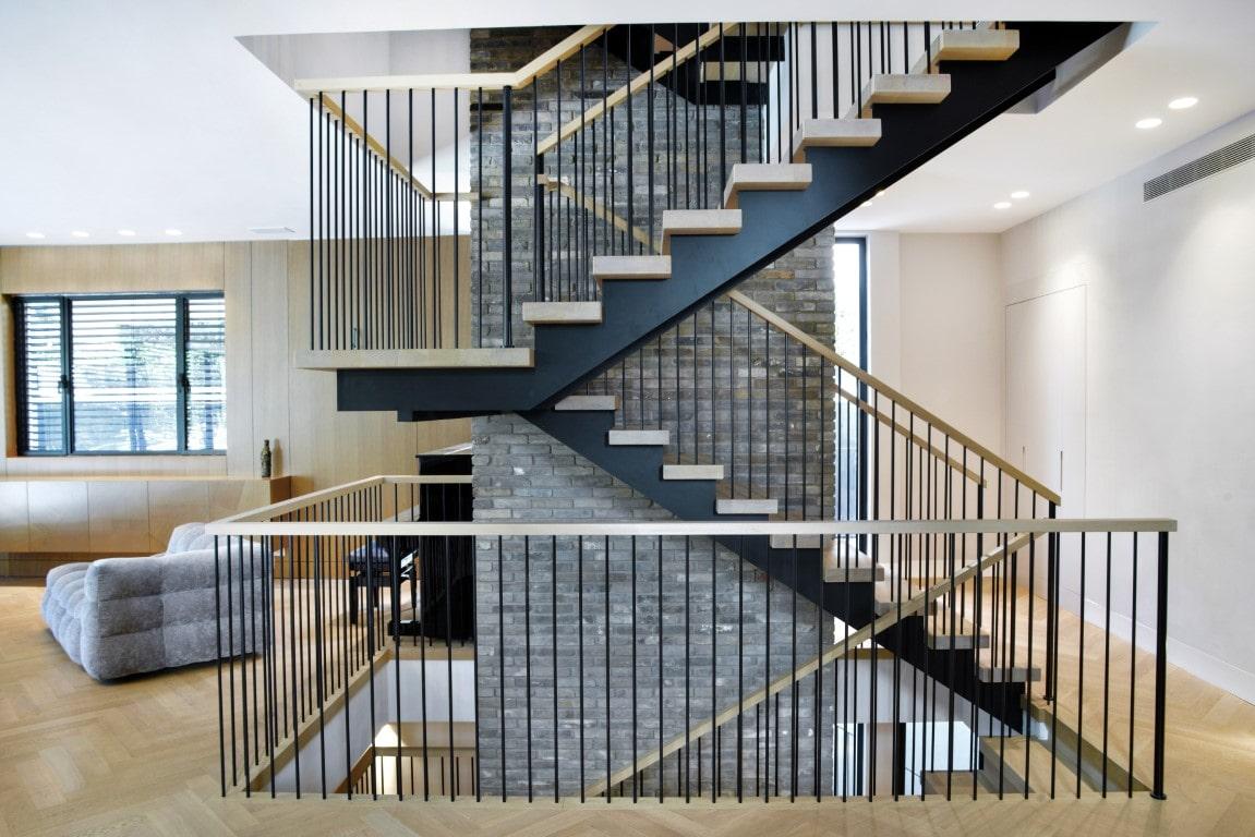 שני גרמי מדרגות עץ וברזל בשחור וגוונים של עץ על רקע פיר מעלית מחופה בבריקים