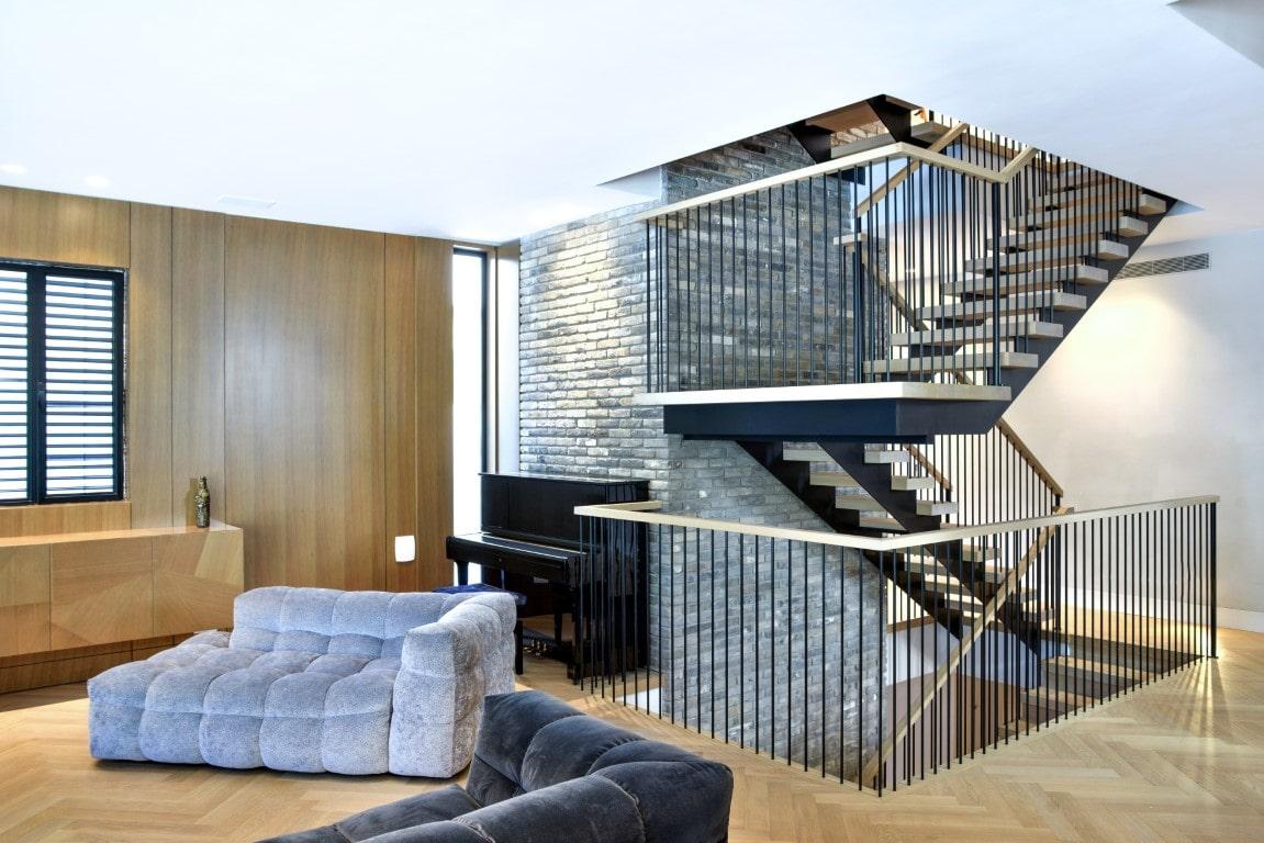 3 גרמי מדרגות ברזל שחור עם מדרכי עץ אלון ומעקה ברזל שחור עם מאחז יד מחבר את קומות הוילה