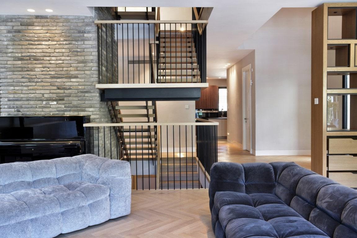 מבט מהסלון על שלושה גרמי מדרגות ברזל עם מדרכי עץ אלון ומעקה ברזל שחור