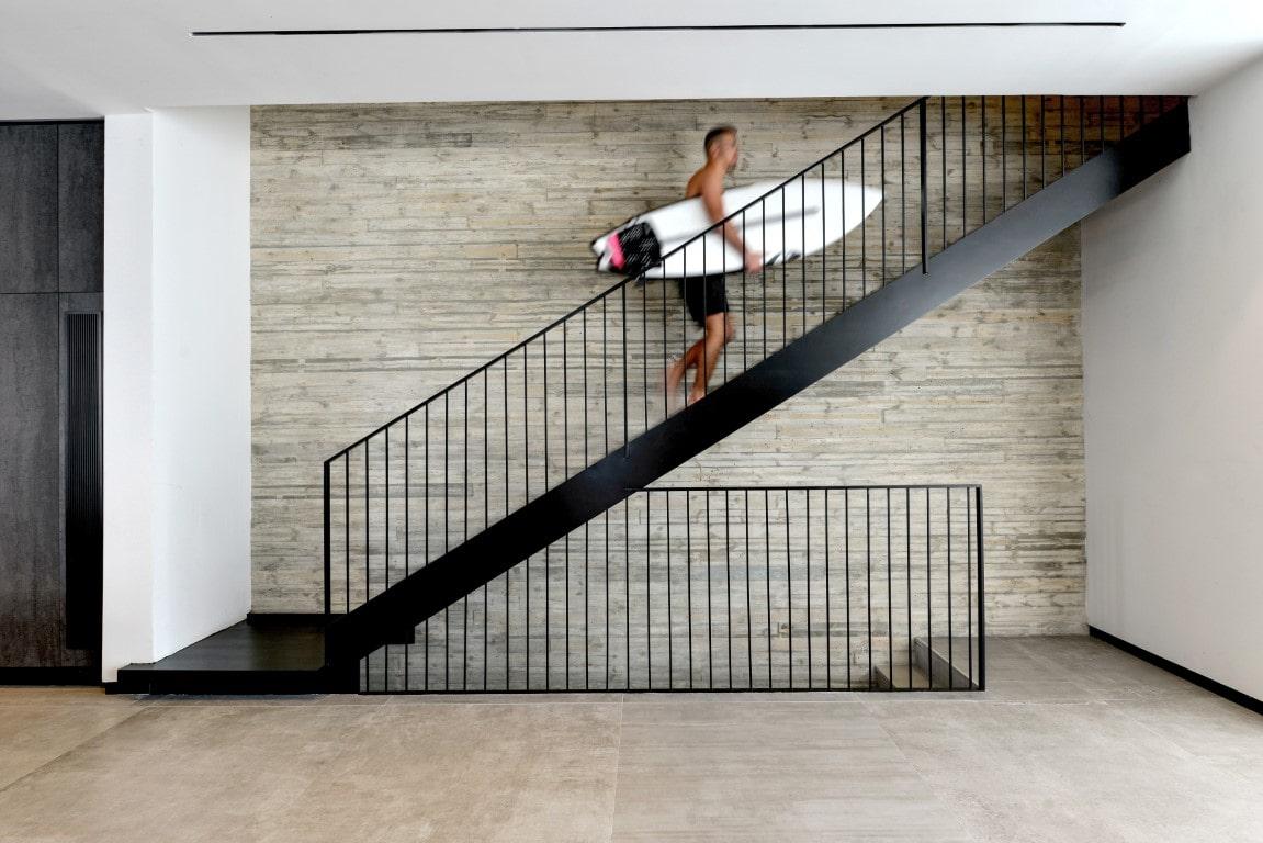 דייר בבית מטפס במעלה גרם המדרגות מברזל שחור