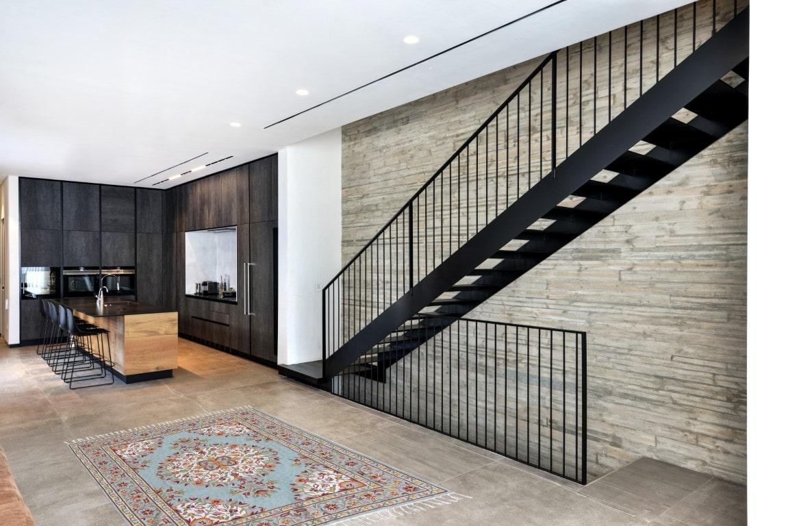 מבט צד על גרם מדרגות מברזל שחור שיוצאות מהסלון המפואר ומחברות בין הקומות של הבית