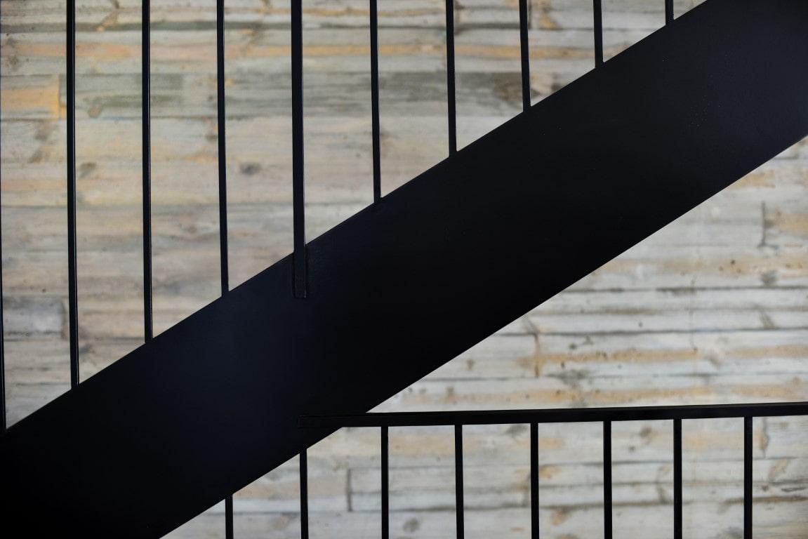 חלקן התחתון של המדרגות מברזל שחור ומעקה הבטיחות