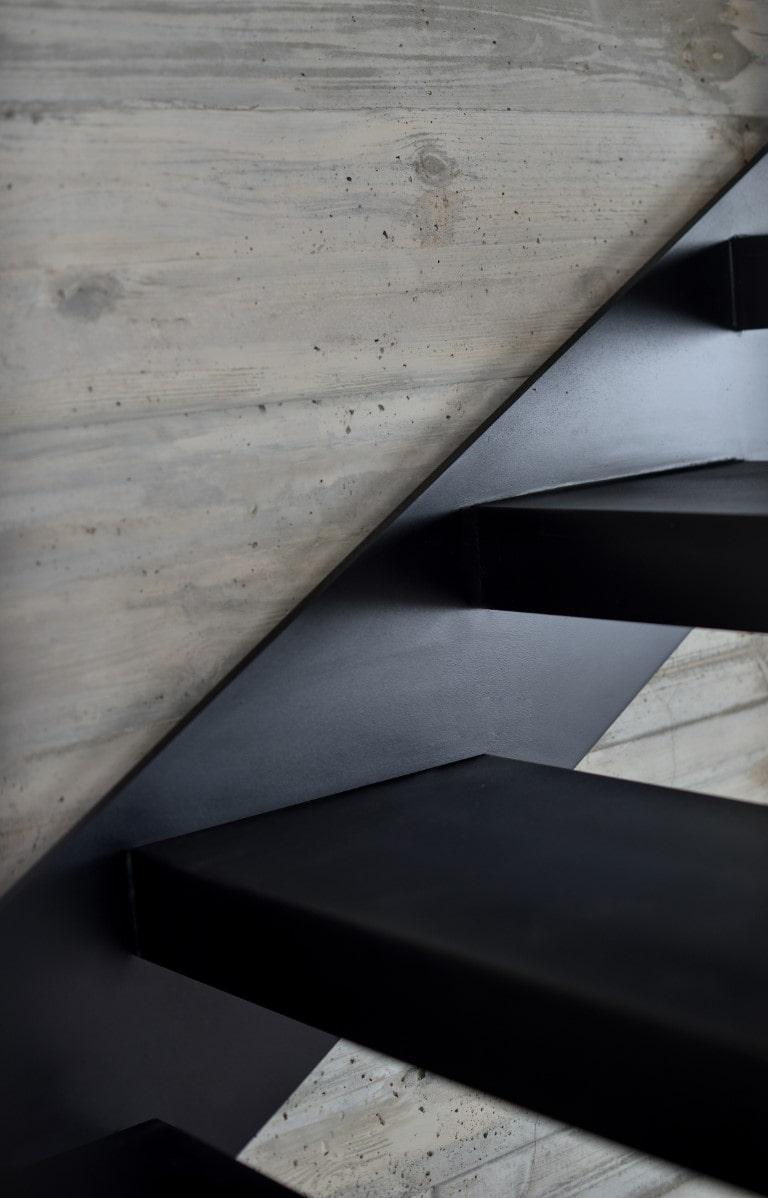 מדרך מדרגות ברזל בשחור על רקע קיר אבן אפור