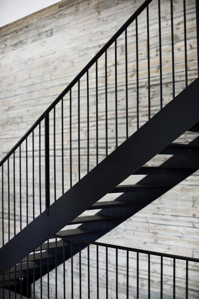 מבט אחורי על גרם מדרגות מברזל שחור עם מעקה ומאחז יד מברזל שחור