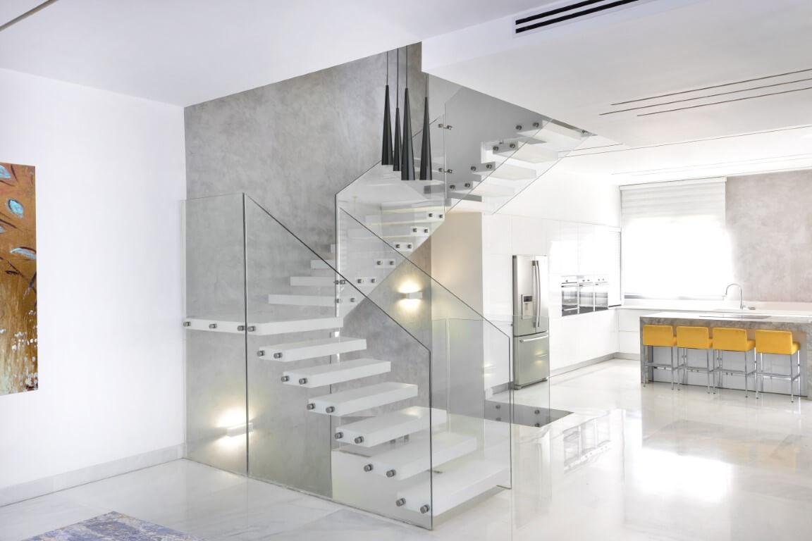 מדרגות צפות מקוריאן לבן בין הסלון ופינת האוכל