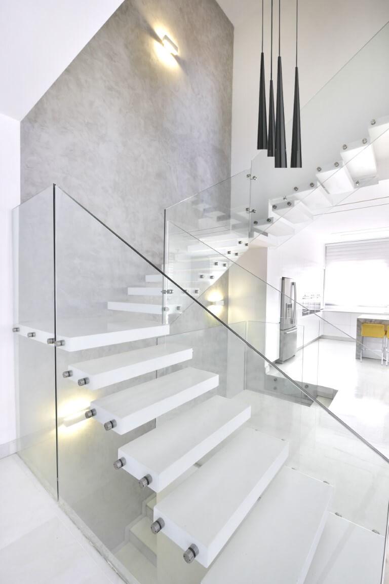 מדרגות מרחפות מקוריאן לבן עם מעקה זכוכית עולות לאוך קיר בגוון אפור צרפתי