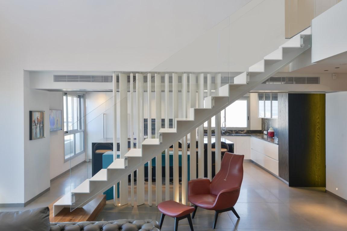 מבט צד על מדרגות מדרגות ברזל צפות בצבע לבן עם מעקה זכוכית
