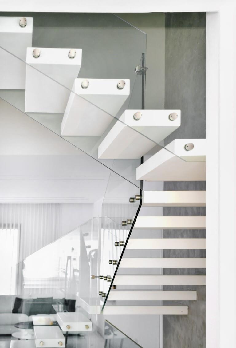 מדרגות מרחפות מקוריאן לבן מבעד למעקה הזכוכית