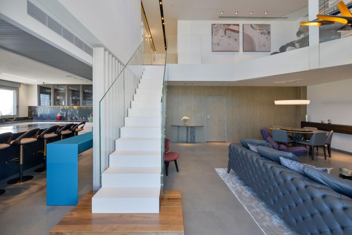 גרם מדרגות ברזל לבן עולה אל הקומה השניה בליווי של מעקה זכוכית שקופה