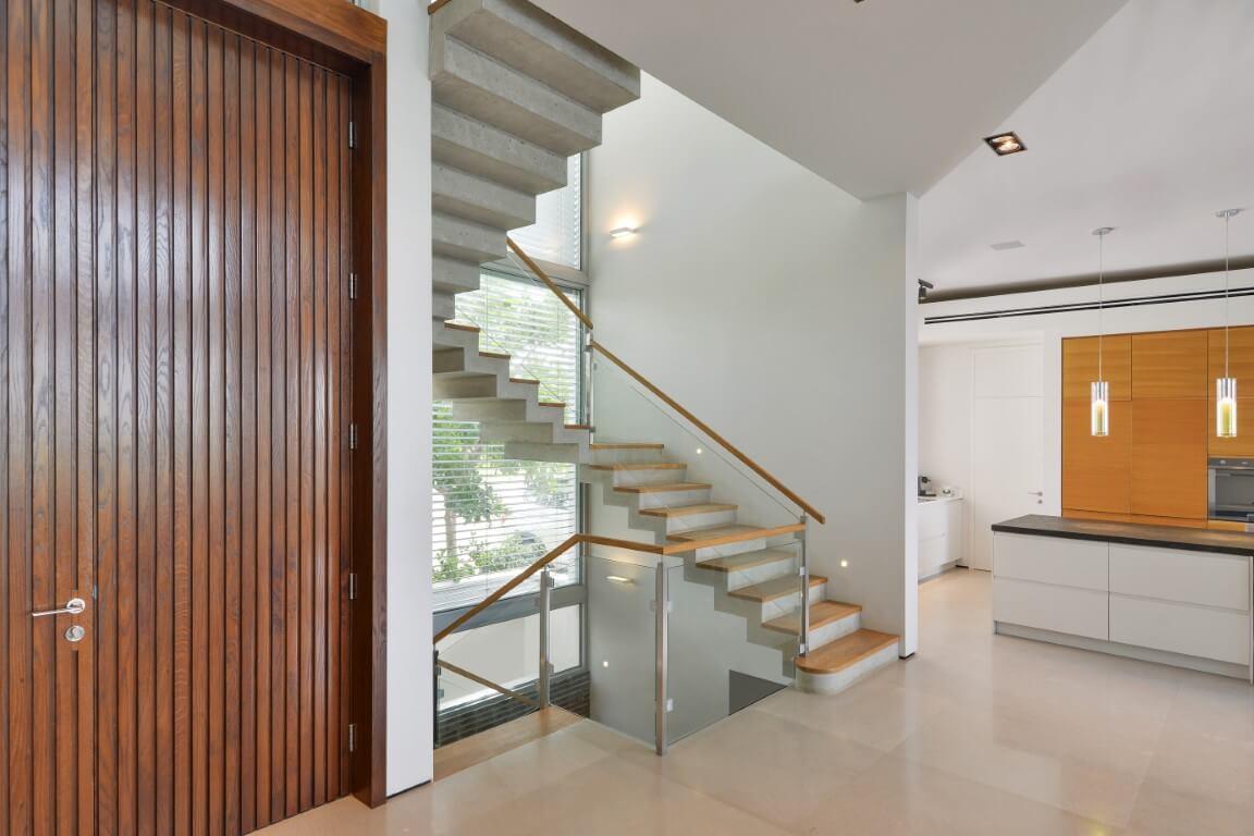 מבט רחב על דלת הכניסה בגוון של עור וקפה המטבח הנקי וגרמי מדרגות העץ שממוקמים בינהם