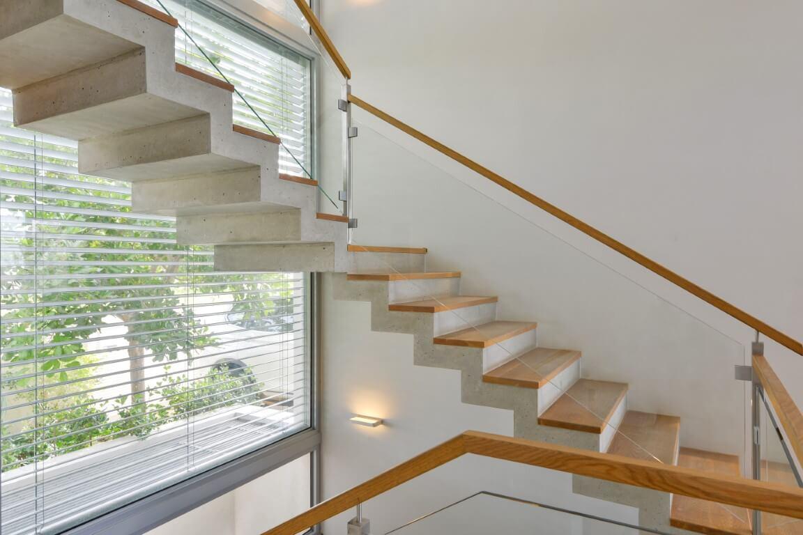 מדרגות עץ אלון בהיר עם מעקה זכוכית מתפתלים ועולים אל המפלס העליון של הוילה