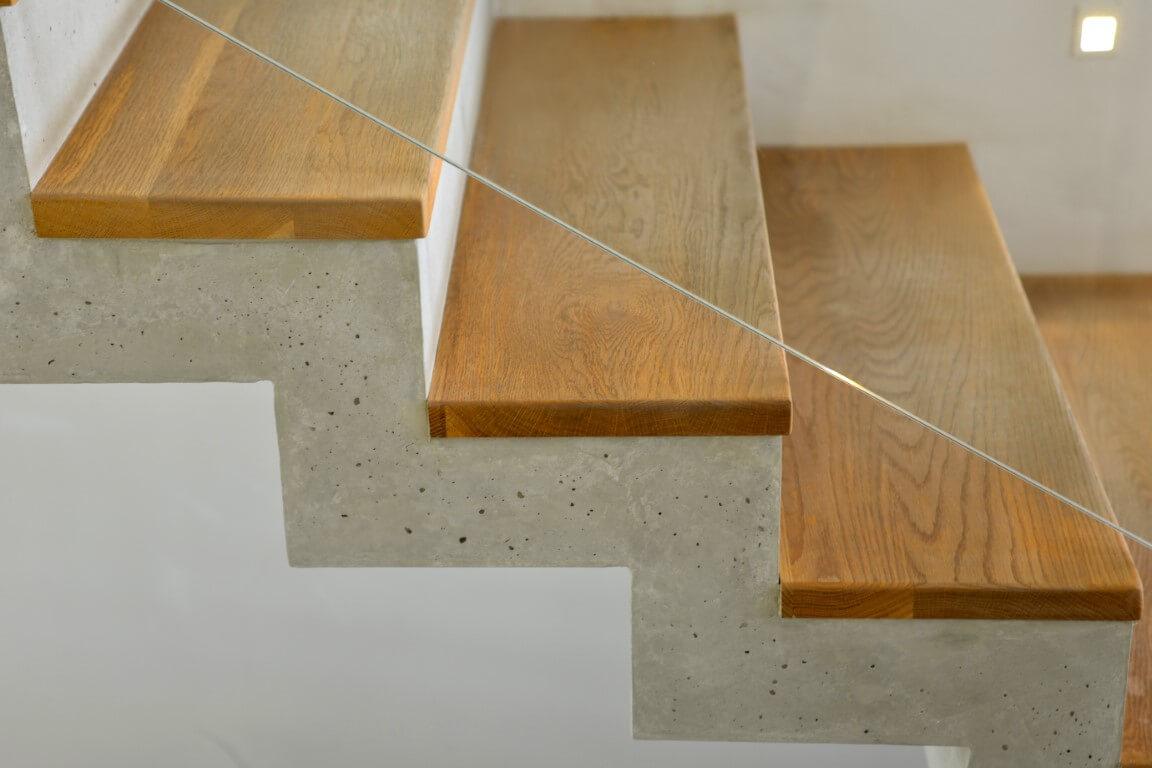 פוקוס על השילוב המושלם בין מדרכי עץ האלון, הבטון והזכוכית של המעקה