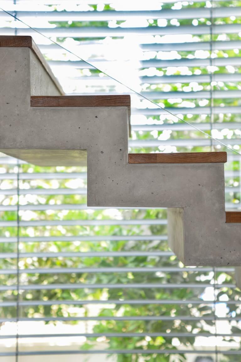 גרם מדרגות על רקע חלון מכוסה תריס שדרכו נראית הגינה של הוילה