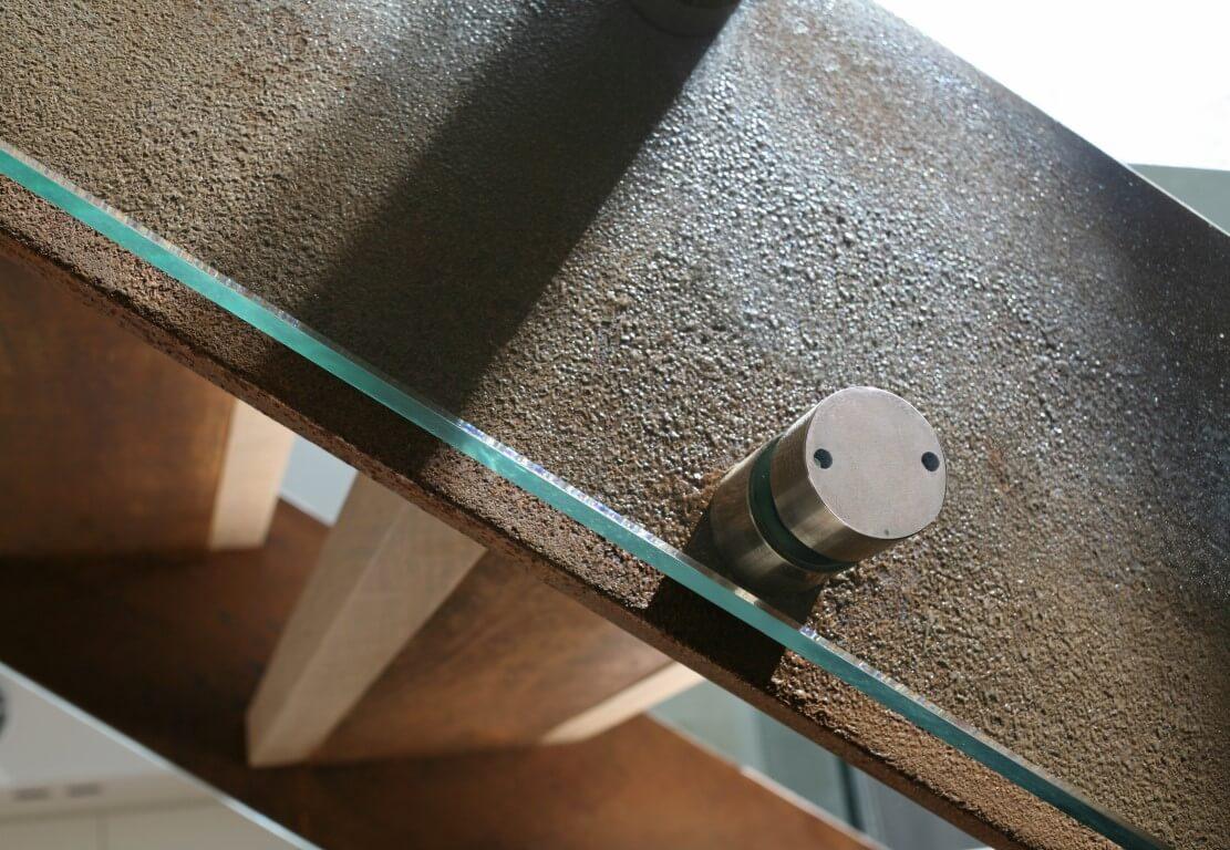 תקריב אל החיבורים של מעקה הזכוכית והמדרגות