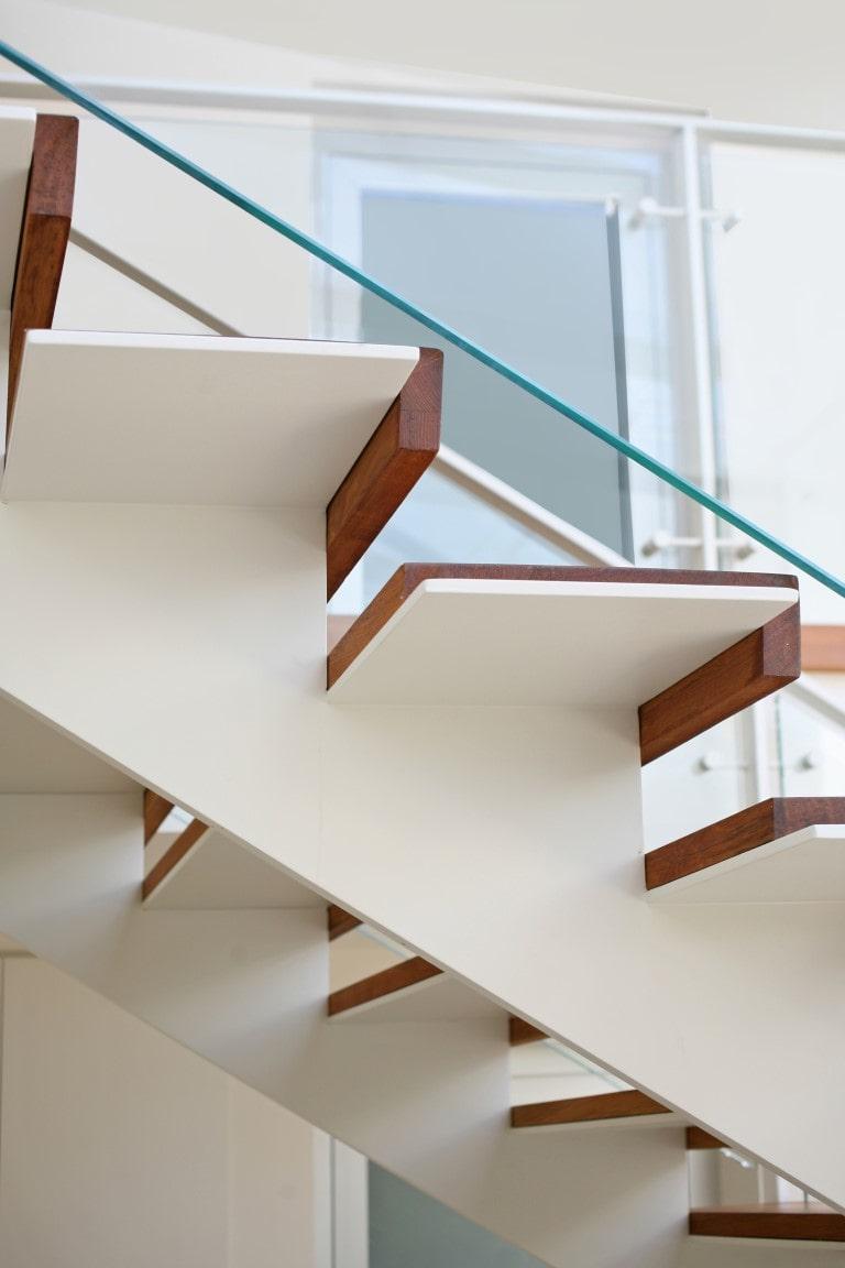 ארבעה מדרכי עץ טבעי על מדרגות ברזל לבן עם מעקה זכוכית שקופה