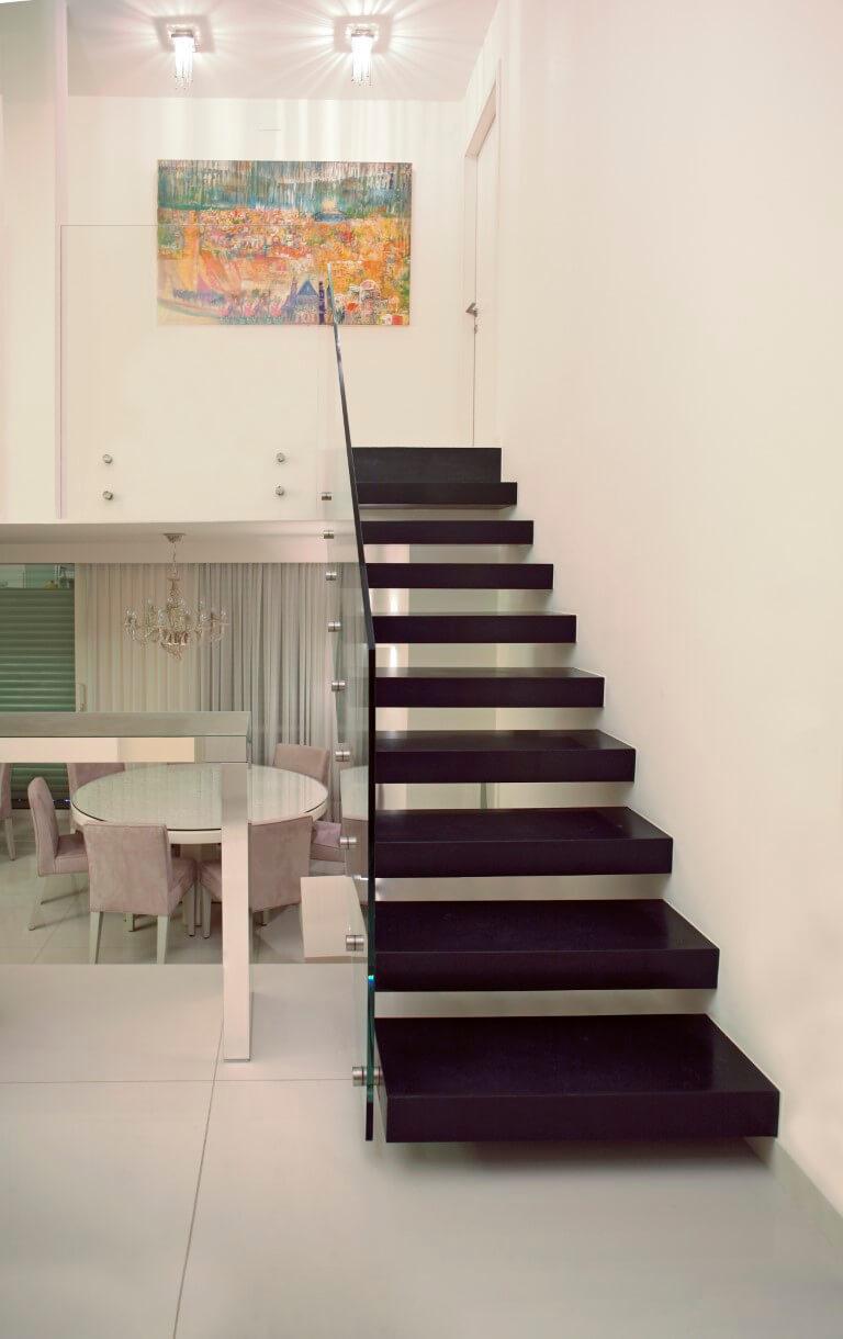 גרם מדרגות צפות עם מדרכי שיש כהה ומעקה זכוכית ליד פינת האוכל