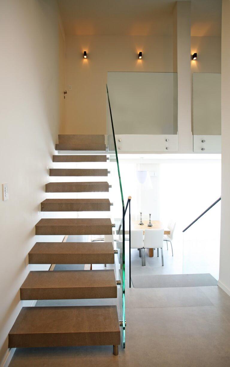 שני גרמי מדרגות מרחפות עם מדרכי עץ ומעקה זכוכית