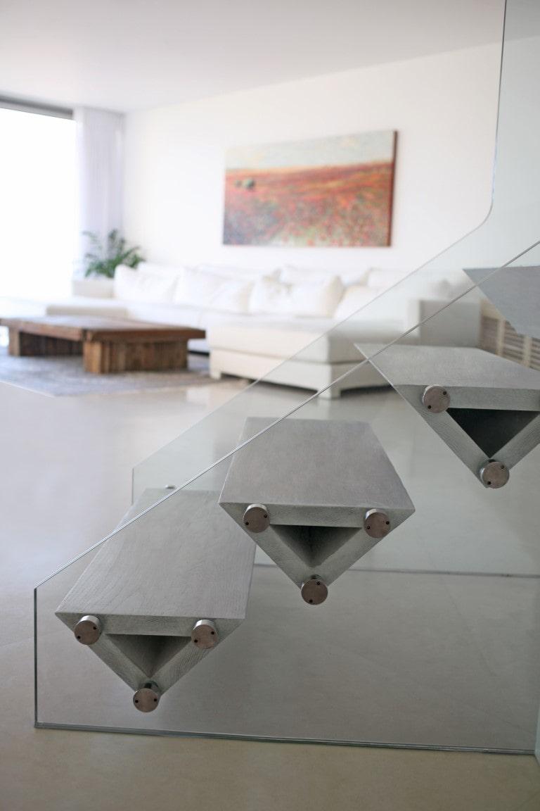 שלושה מדרכי עץ משולשים מאלון אמריקאי מולבן יושבים בין מעקות זכוכית שקופה על רקע סלון מינימליסטי בלבן
